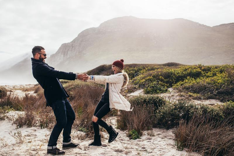 Beautiful couple dancing along the beach on winter day stock photos