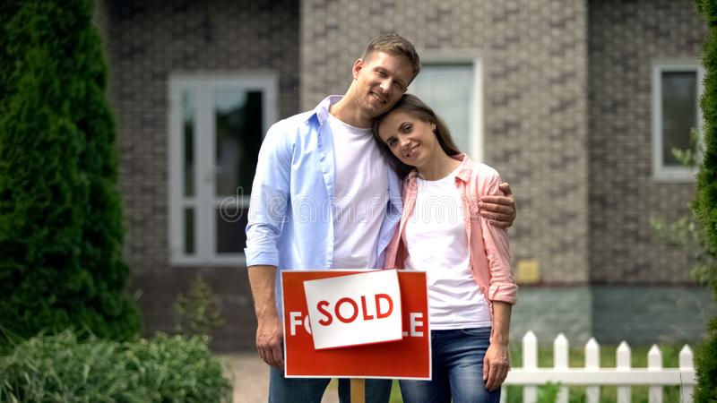 Beautiful couple hugging and smiling on background of luxury house, investment stock images