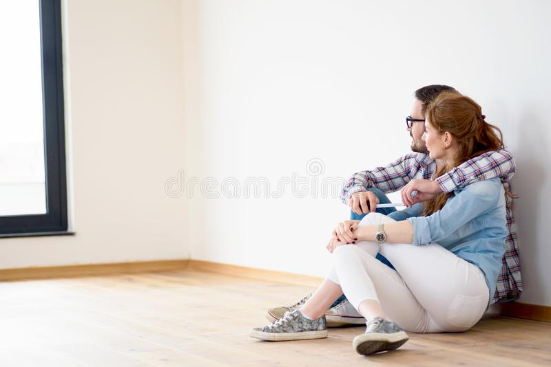 Beautiful couple just moved into new empty apartment sitting on the floor. Activities after relocation. stock images