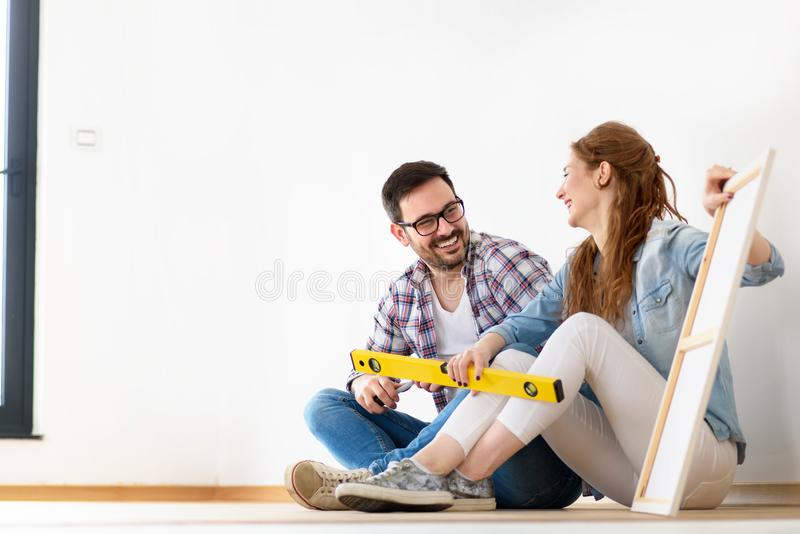 Beautiful couple just moved into new empty apartment sitting on the floor. Activities after relocation. royalty free stock images