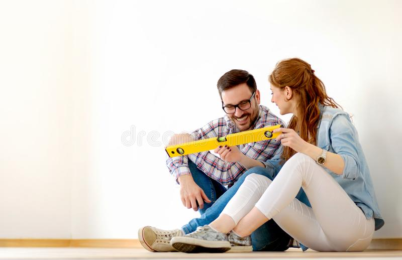 Beautiful couple just moved into new empty apartment sitting on the floor. Activities after relocation. royalty free stock photos