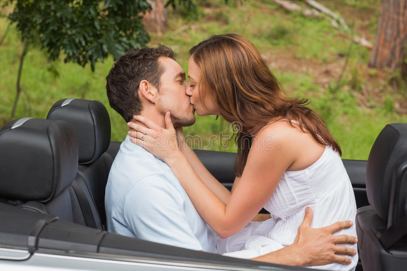 Beautiful couple kissing in back seat royalty free stock image