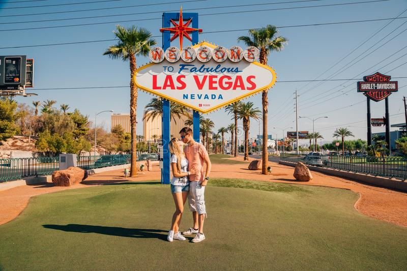 Beautiful couple kissing by the Las Vegas sign in Nevada. During sunny day stock photo