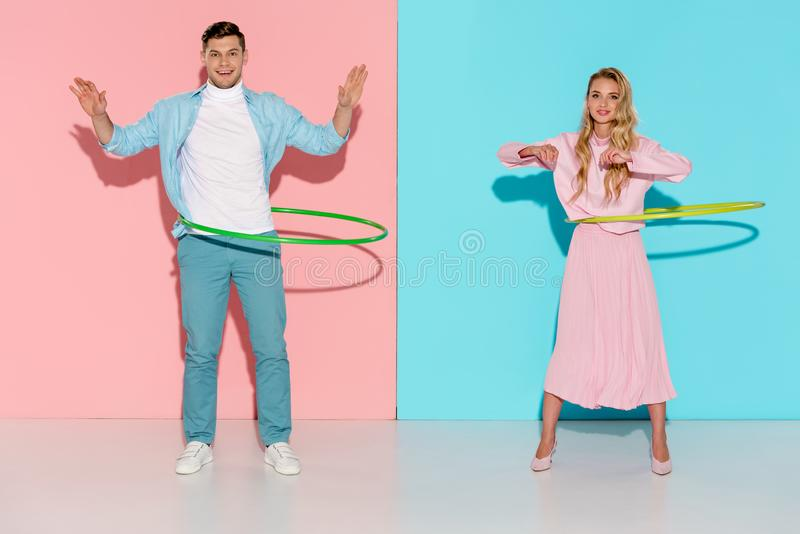 Beautiful couple looking at camera and exercising with hula hoops. On pink and blue background stock photos