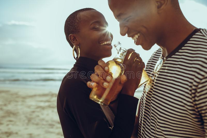 Beautiful couple in love at beach. Beautiful couple in love drinking beers at the beach. Smiling young men and women standing at the beach having beers stock images