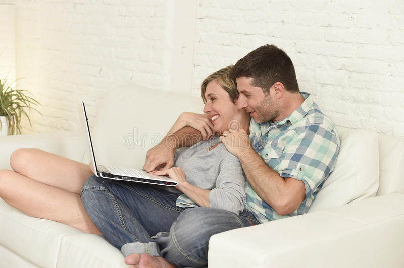 Beautiful couple in love on couch together with laptop computer happy at home using internet. Young attractive 30s couple in love sitting on couch together with royalty free stock images