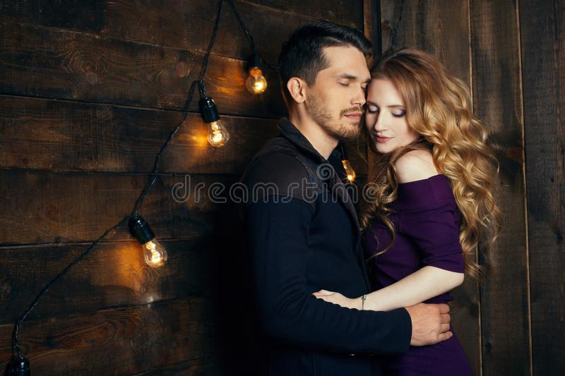Beautiful couple in love hugging against the background of glowing lights. Studio portrait photo of a girl blondes and a guy with stock image