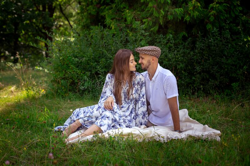 Beautiful couple in love at the picnic smiles each others royalty free stock photos