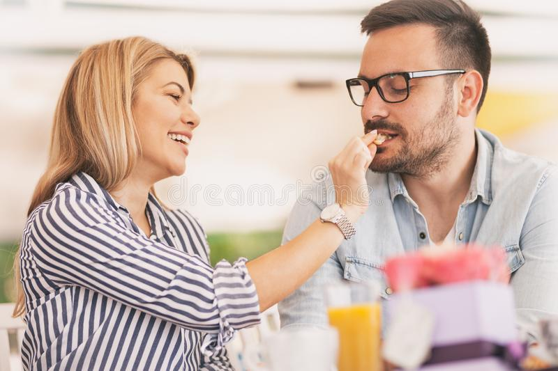 Beautiful couple in love is sitting in cafe and eating croissants royalty free stock photo