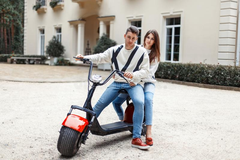 Beautiful couple in love with stylish fashion clothes riding stock photo