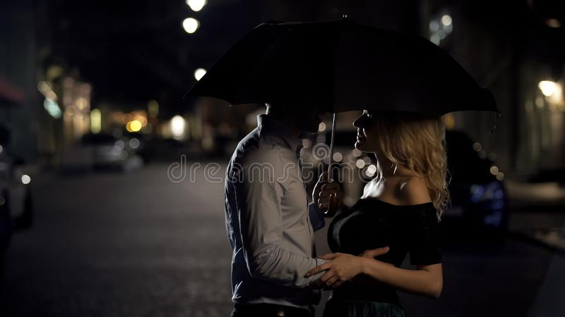 Beautiful couple of lovers embracing under umbrella, night date, love story royalty free stock images