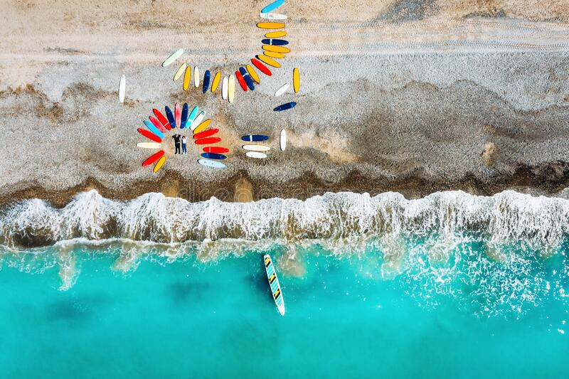 A beautiful couple is lying on the beach of France next to surfboards, shooting from a quadcopter, a lot of surfboards. Are unusually lying on the beach stock images