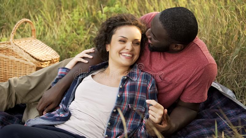 Beautiful couple lying in park dreaming about marriage and happy bright future stock photo