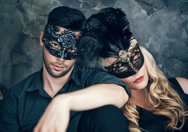 Beautiful couple in mysterious black mask sitting on floor in studio. Fashion, party concept stock images