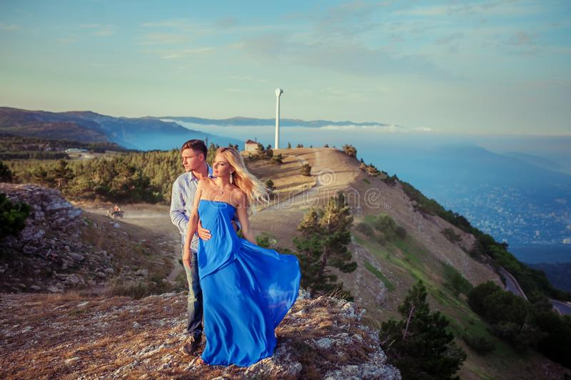 Beautiful couple of newlywed hugging at wedding day on cliff with ocean view. Stylish bride and elegant groom look at stock images