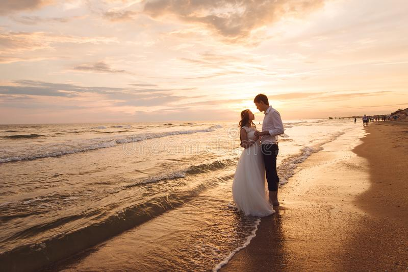 A beautiful couple of newlyweds, the bride and groom walking on the beach. Gorgeous sunset and sky. Wedding dresses, a. White luxury dress for a girl. Family royalty free stock photography