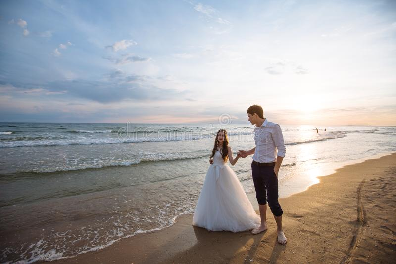 A beautiful couple of newlyweds, the bride and groom walking on the beach. Gorgeous sunset and sky. Wedding dresses, a. White luxury dress for a girl. Family stock image
