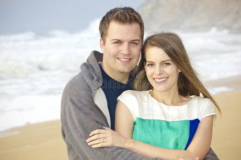 Beautiful Couple Portrait on the Beach. A portrait of a beautiful young couple enjoying an afternoon at the beach royalty free stock photo