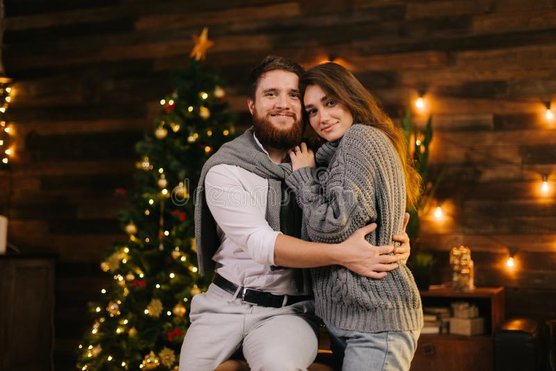 Beautiful couple posing against the background of a Christmas tree. stock photo