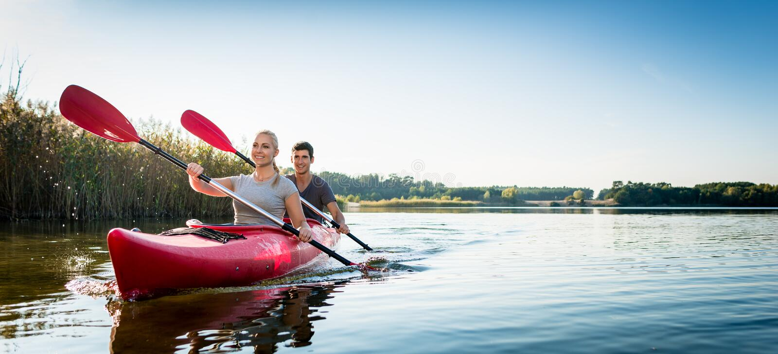 Beautiful couple sailing kayak on lake stock image