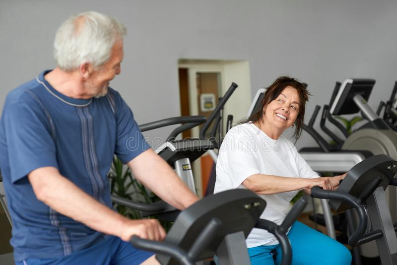 Beautiful couple of seniors working out at gym. royalty free stock photography