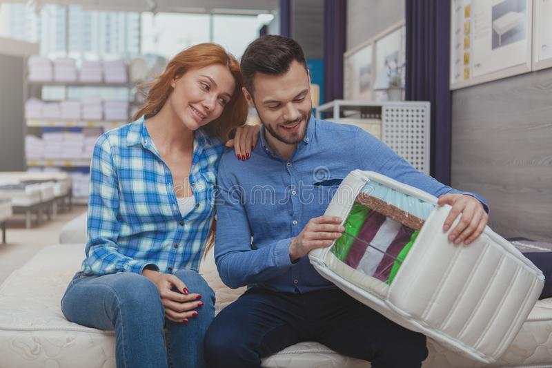 Beautiful couple shopping for new mattress at furnishings store royalty free stock photo