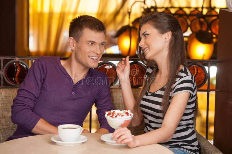 Beautiful couple sitting in cafe and eating. royalty free stock photo