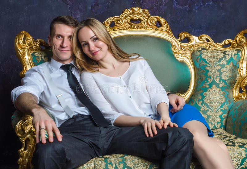 Beautiful couple sitting on classic sofa. Girl and boy on green sofa. Happy married couple. Successful people in vintage interior royalty free stock photos