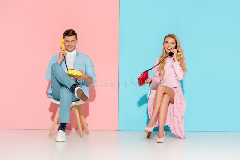 Beautiful couple sitting and having conversation on vintage telephones. With pink and blue background royalty free stock images