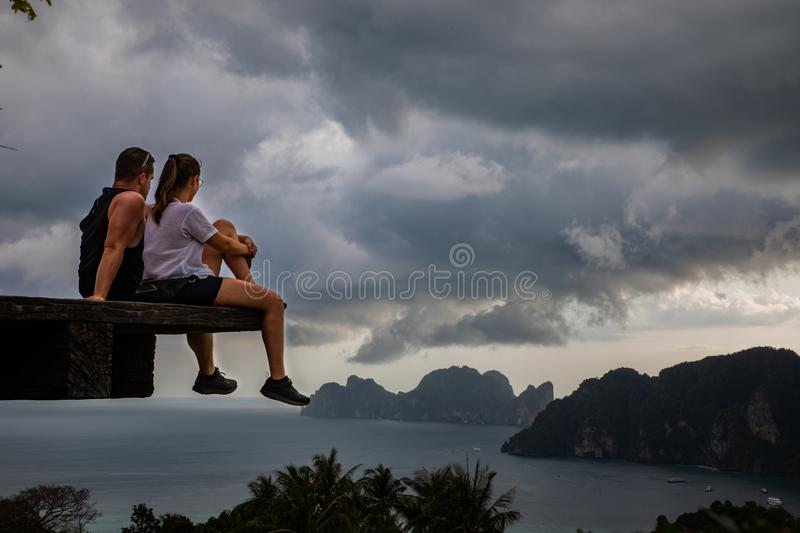 Beautiful couple sitting on wooden platform with Phi Phi island views and cloudy sky royalty free stock photo