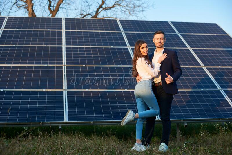 Beautiful couple by a solar panel stock photo
