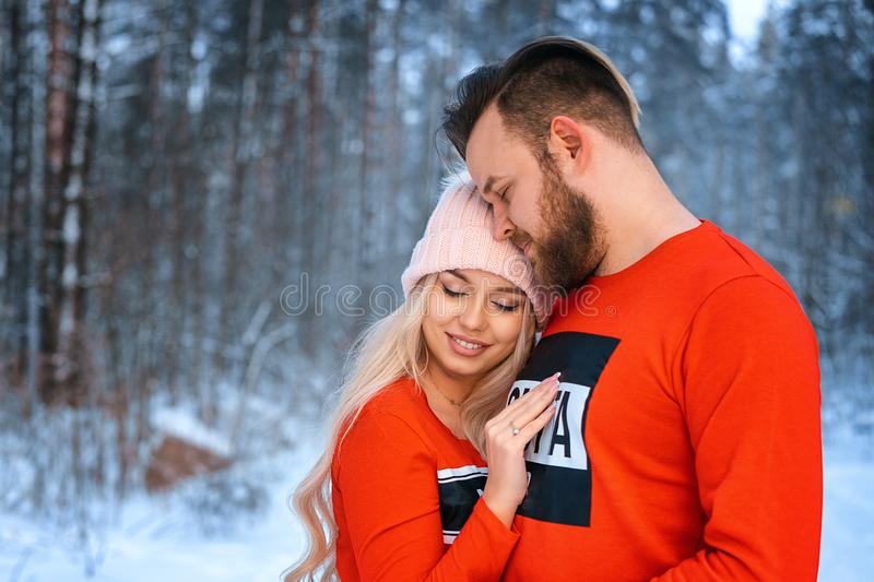 Beautiful couple standing arm in arm in the red sweater in the background of the forest in winter , a walk in the winter woods. / stock photos