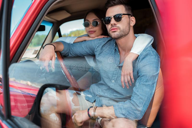 Beautiful couple in sunglasses sitting in car. And hugging together royalty free stock photo