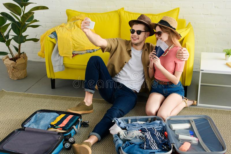 beautiful couple taking selfie on smartphone while packing suitcases royalty free stock image