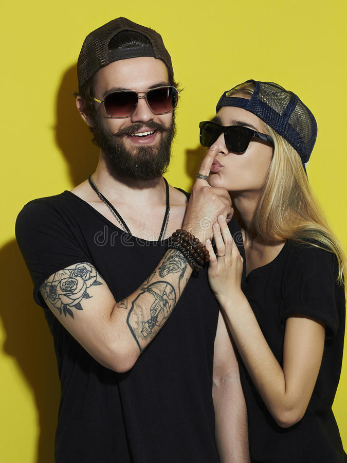Beautiful couple together. Tattoo Hipster boy and girl. Bearded young men and blonde in sunglasses.Yellow background royalty free stock photos