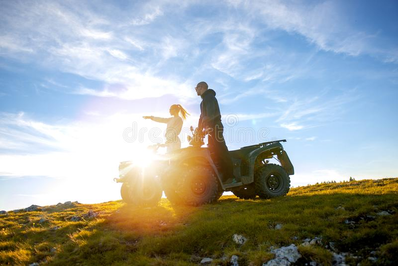 Beautiful couple is watching the sunset from the mountain sitting on atv quadbike royalty free stock images