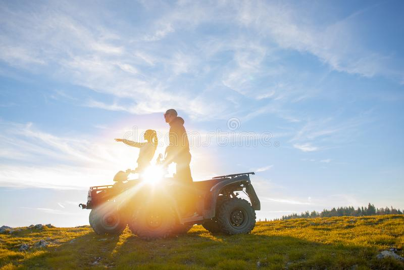 Beautiful couple is watching the sunset from the mountain sitting on atv quadbike royalty free stock photography