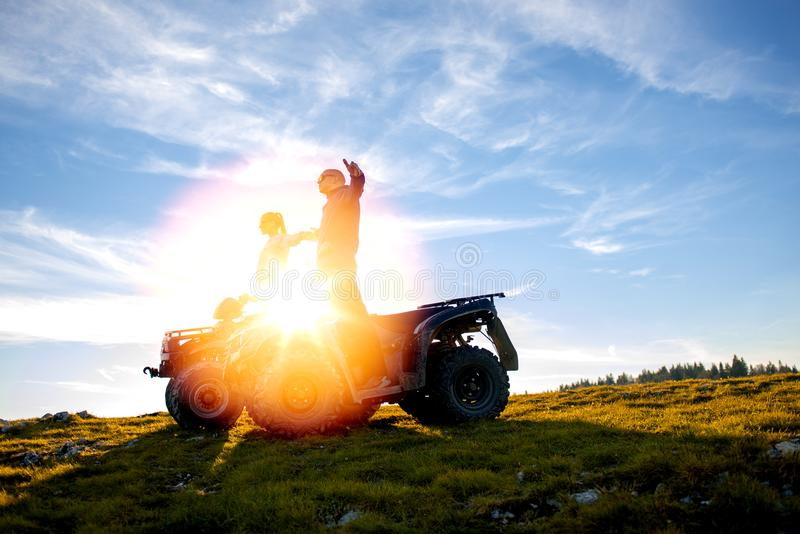 Beautiful couple is watching the sunset from the mountain sitting on atv quadbike stock photography