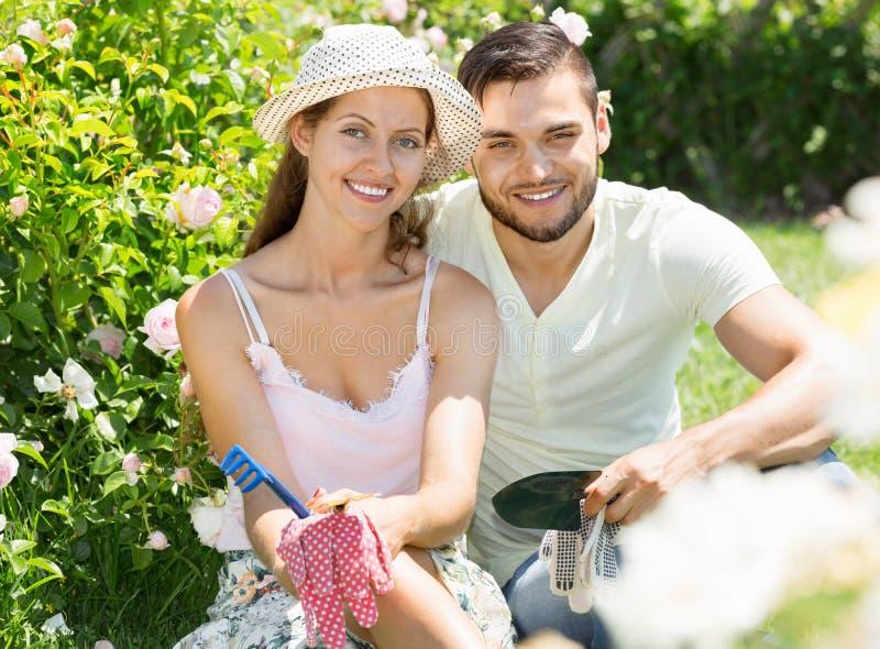 Beautiful couple working in garden. Beautiful happy couple working in the flower garden royalty free stock photos