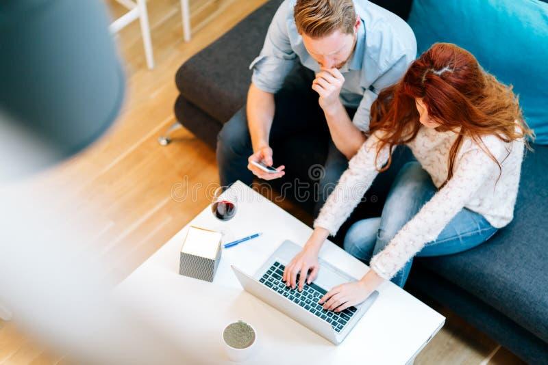 Beautiful couple working on laptop. Beautiful business couple working on laptop in modern cosy room royalty free stock photography
