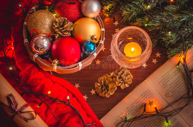 Beautiful cozy christmas scene with xmas tree branch, a small basket with colorful balls, a burning candle, opened book, a garland royalty free stock image