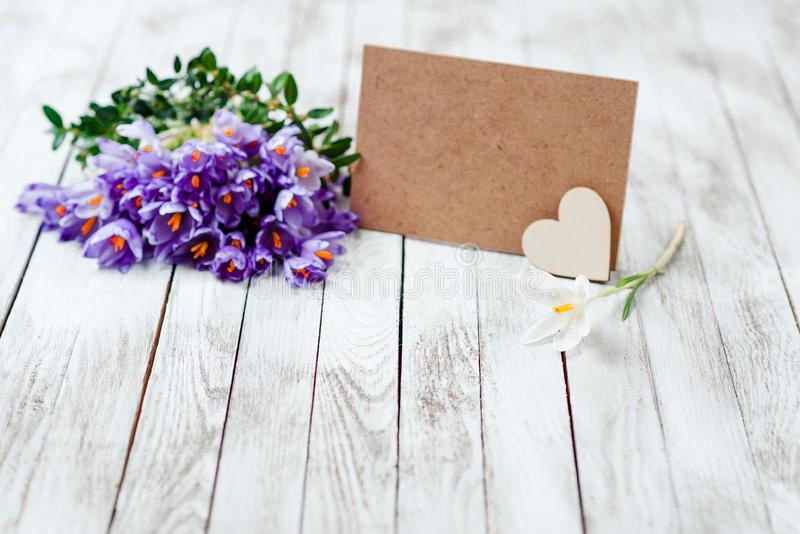 Beautiful crocus flowers in a basket near empty card for your text on wooden background. stock photography
