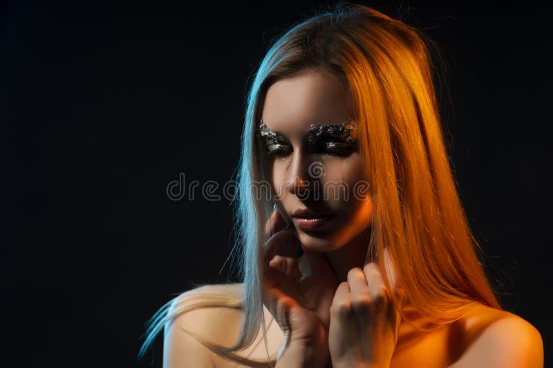 Beautiful crying naked blonde girl, covers topless big chest wit. H her hands. Avant-garde makeup, eyebrows made of aluminum foil. Dark background. Conceptual stock photos