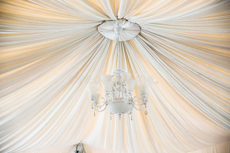 Beautiful crystal chandelier in a white hall. Beautiful crystal chandelier in a white hal, with the cloth stock photos