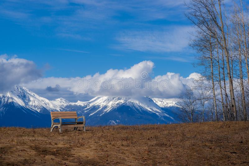 Clouds, Forests Mountains and a Bench in early Spring. Beautiful cumulus clouds have formed over the mountains still covered in snow. A bench is symbolizing a stock images