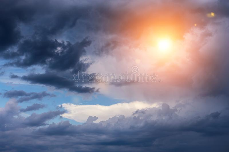 Beautiful cumulus storm dark clouds background with sun and sunlight. Darkness and light royalty free stock photo
