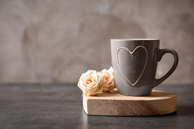 Beautiful cup with heart and roses. On table stock images