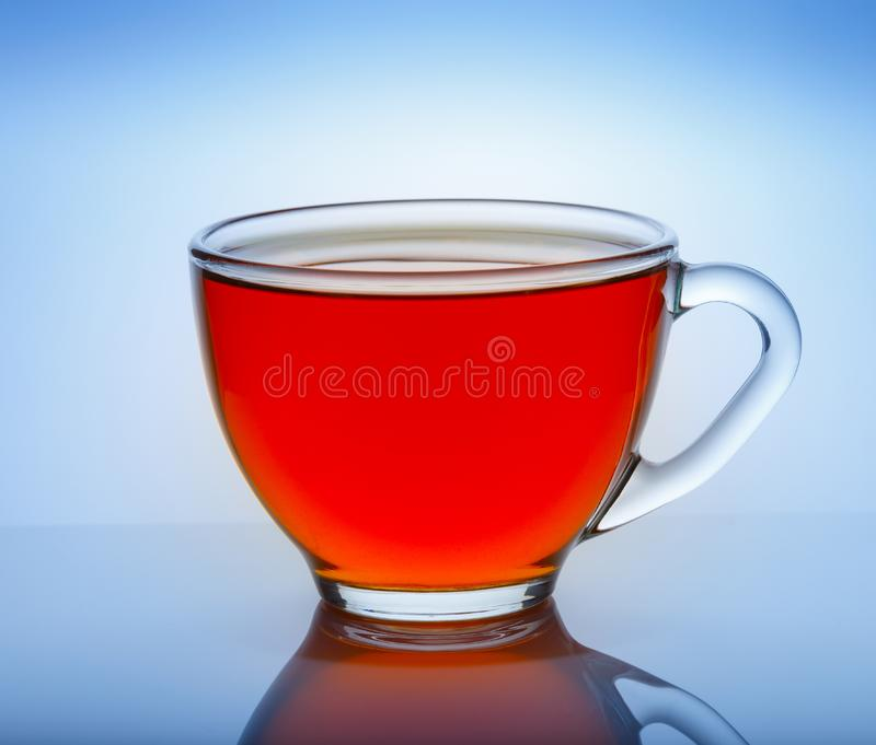 Beautiful cup of tea with reflection on a blue background royalty free stock photo