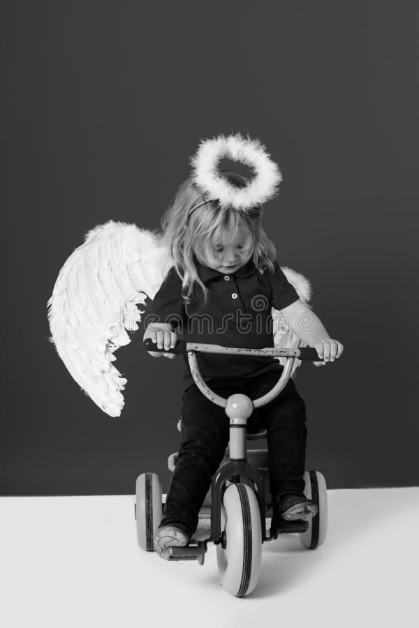 Angel boy for valentine greeting, beautiful cupid on bike. Beautiful cupid on bike with blonde hair and halo, angel boy on red background for valentine greeting stock photography