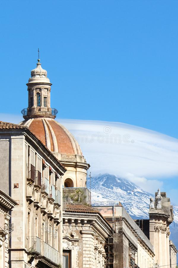 Beautiful Cupola of Saint Agatha Cathedral in Catania, Sicily, Italy captured on a vertical photo with famous volcano Mount Etna. In the background. White stock photos